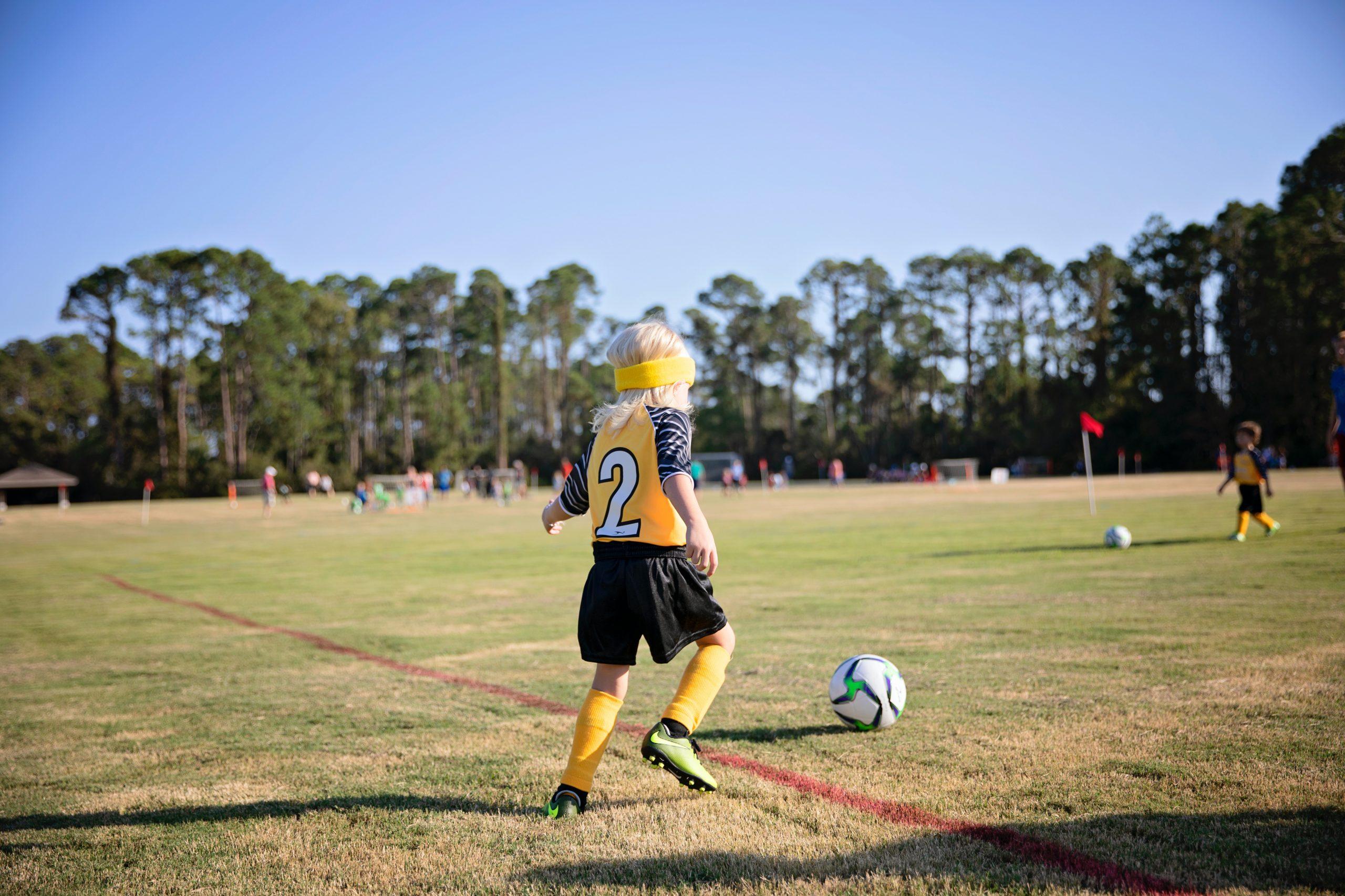 Foto de uma criança na linha de fundo de um campo de futebol correndo em direção a bola.