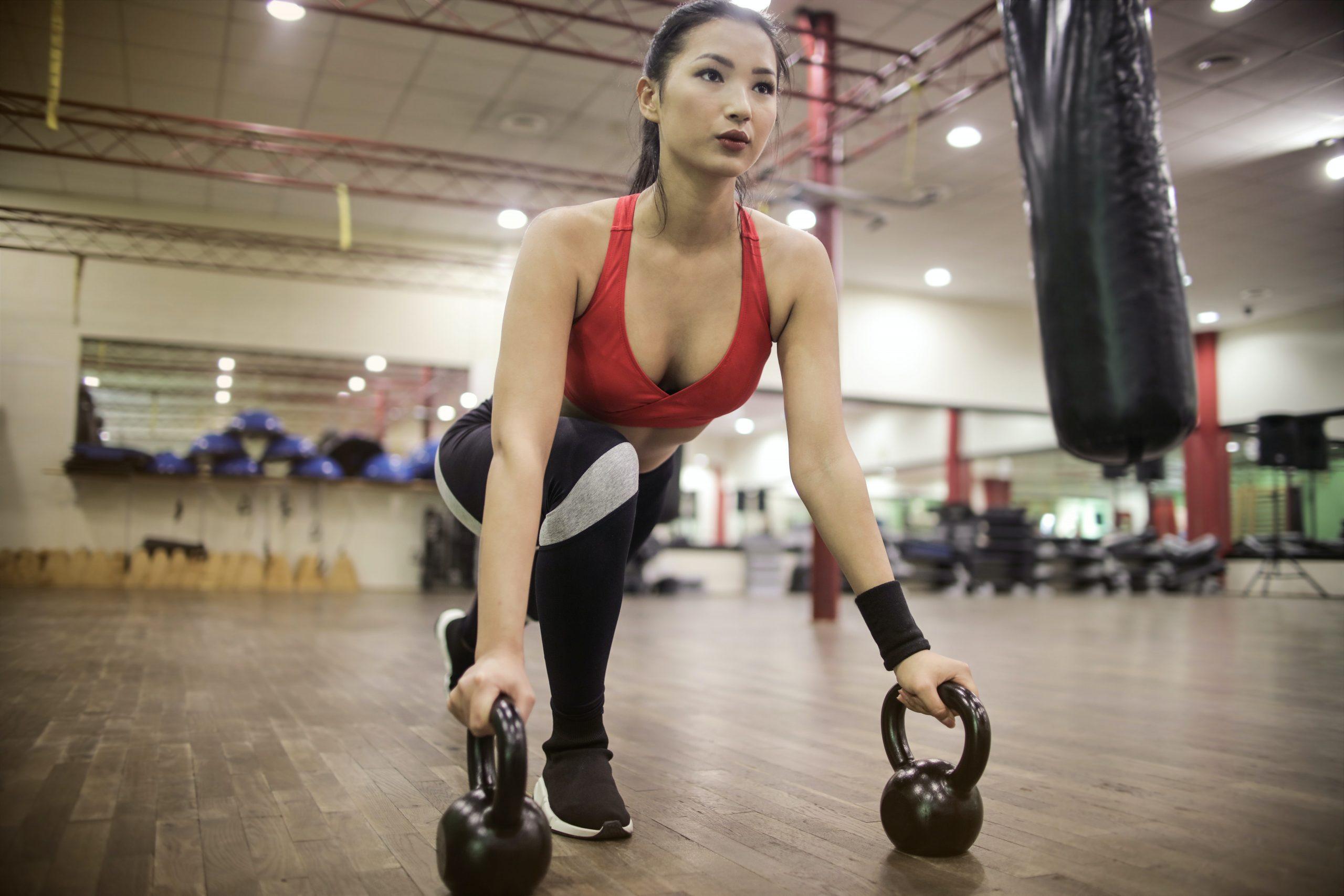 Mulher na academia se alongando com um kettlebell em cada mão