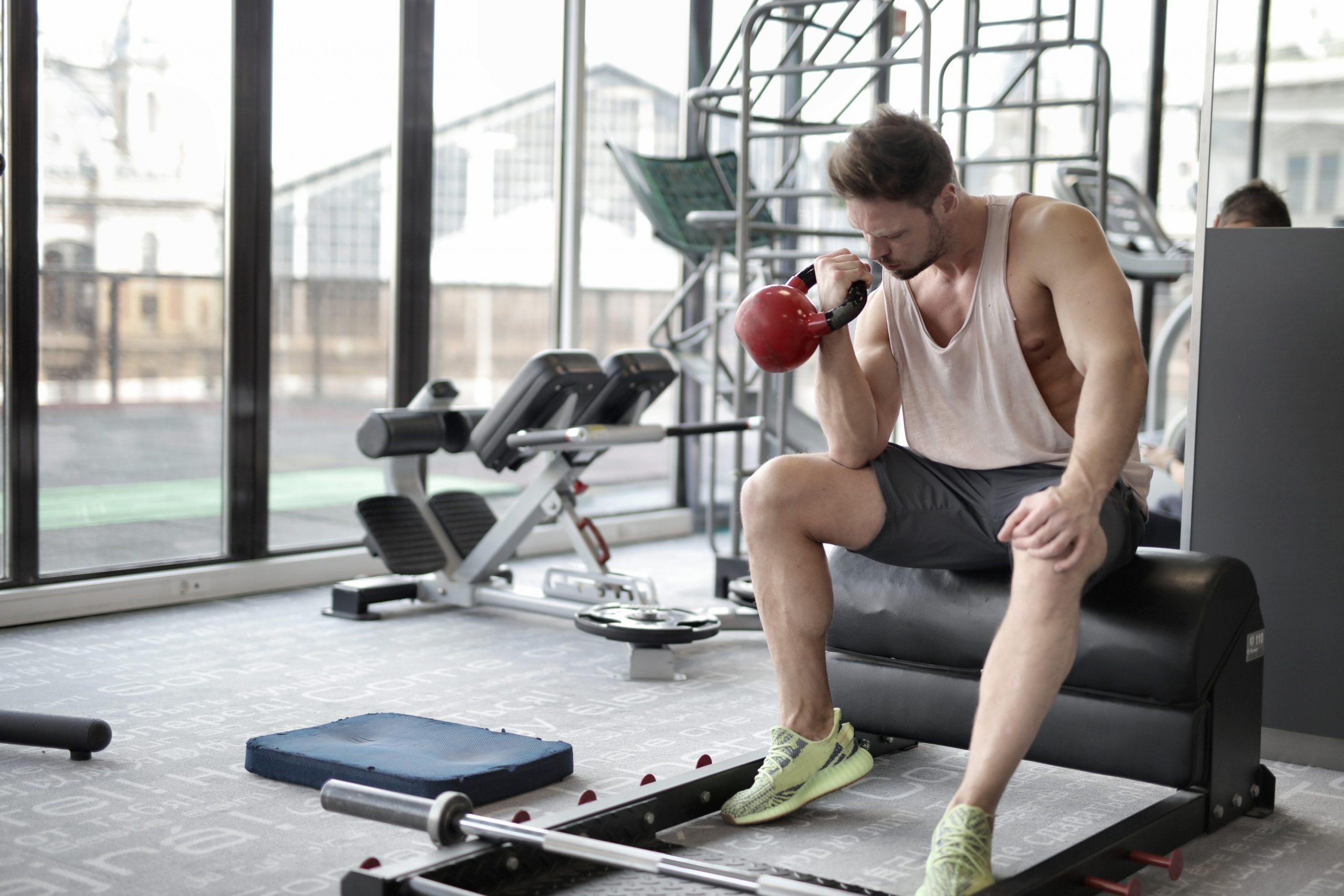 Homem sentado na academia levantando um kettlebell