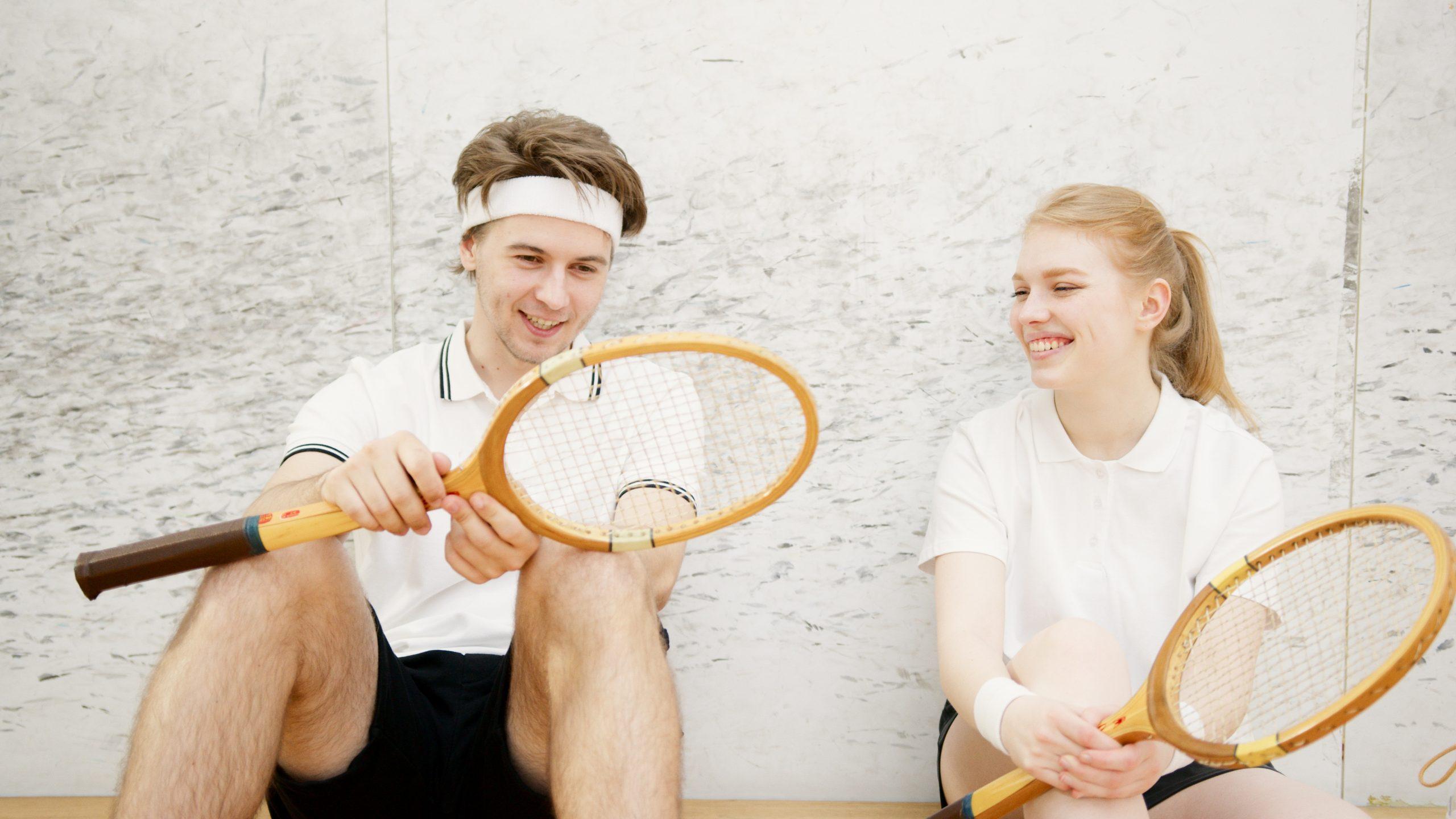 Homem e mulher sentados no chão, encostados na parede olhando e sorrindo para uma raquete de squash