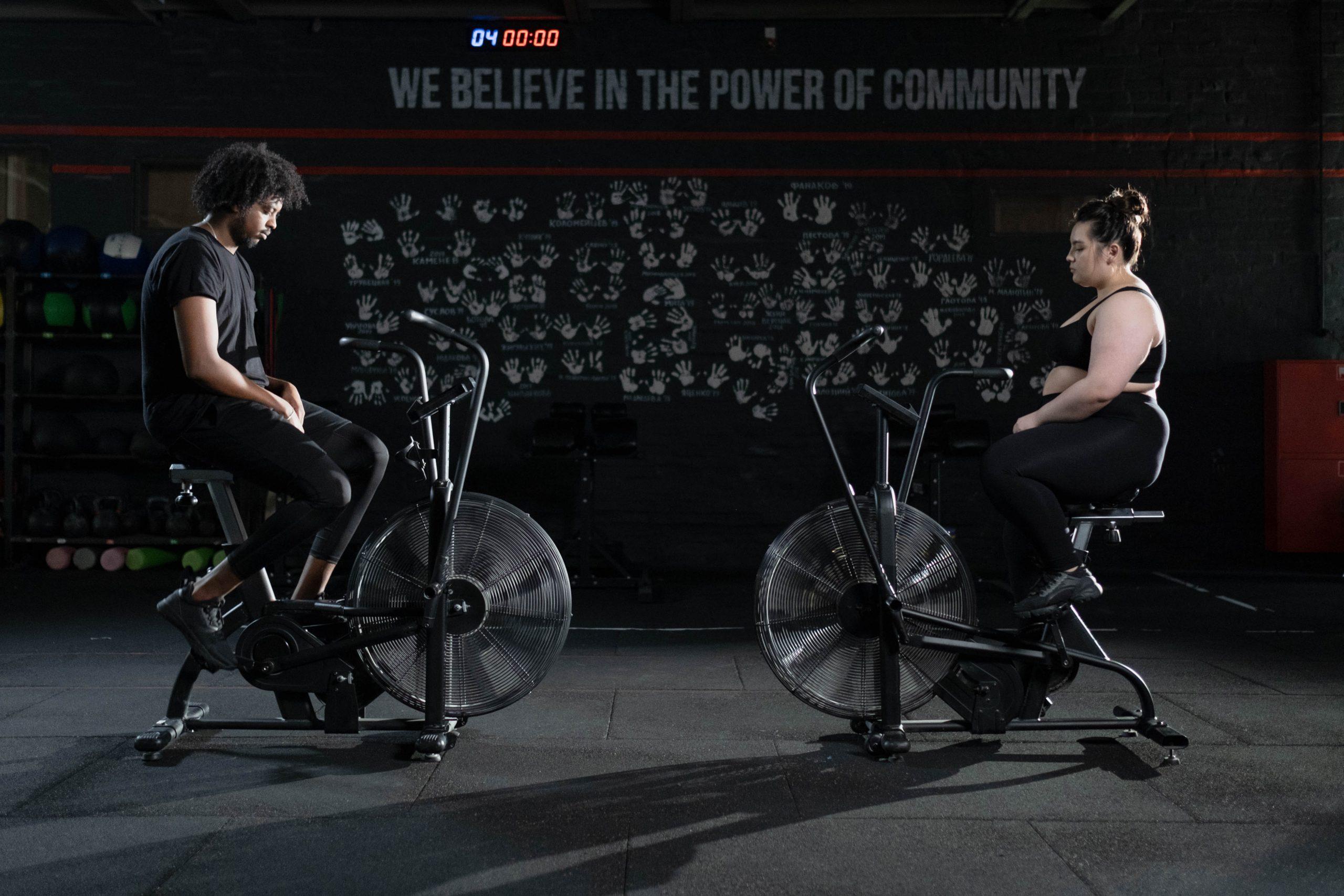 Homem e mulher sentados em air bikes. Um está de frente para o outro.