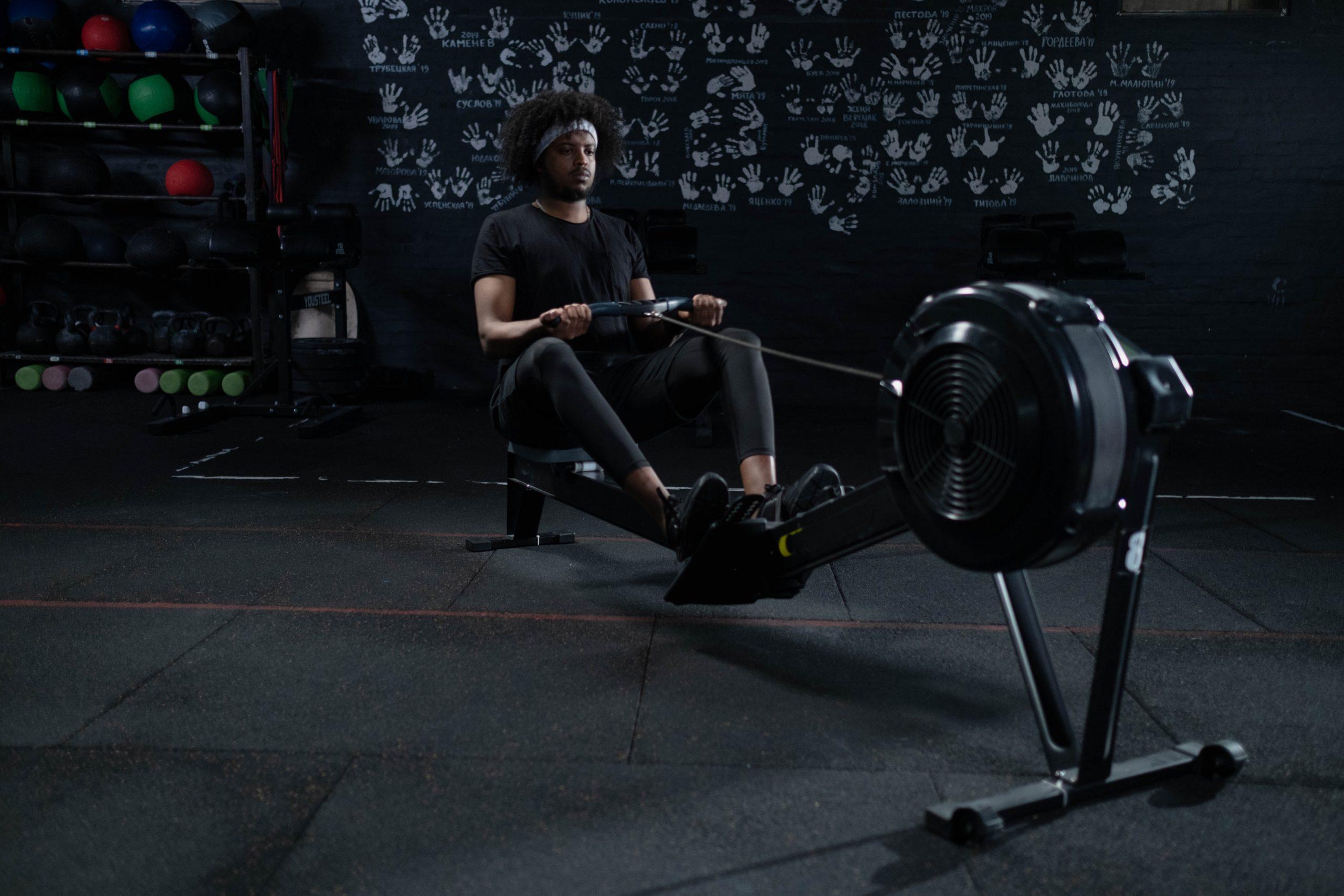 Homem em uma academia sentado no simulador de remo, usando o aparelho para praticar atividades físicas