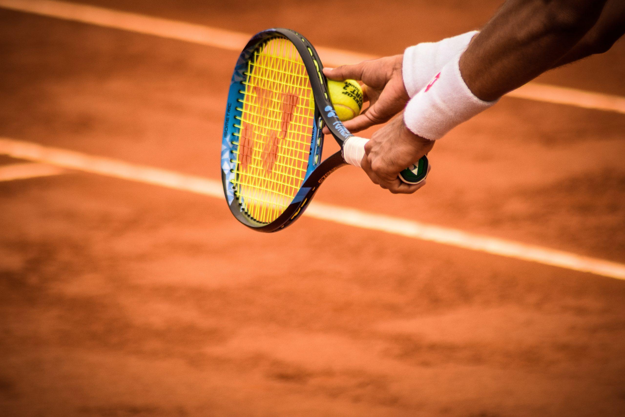 Pessoa jogando tênis segurando raquete e bolinha