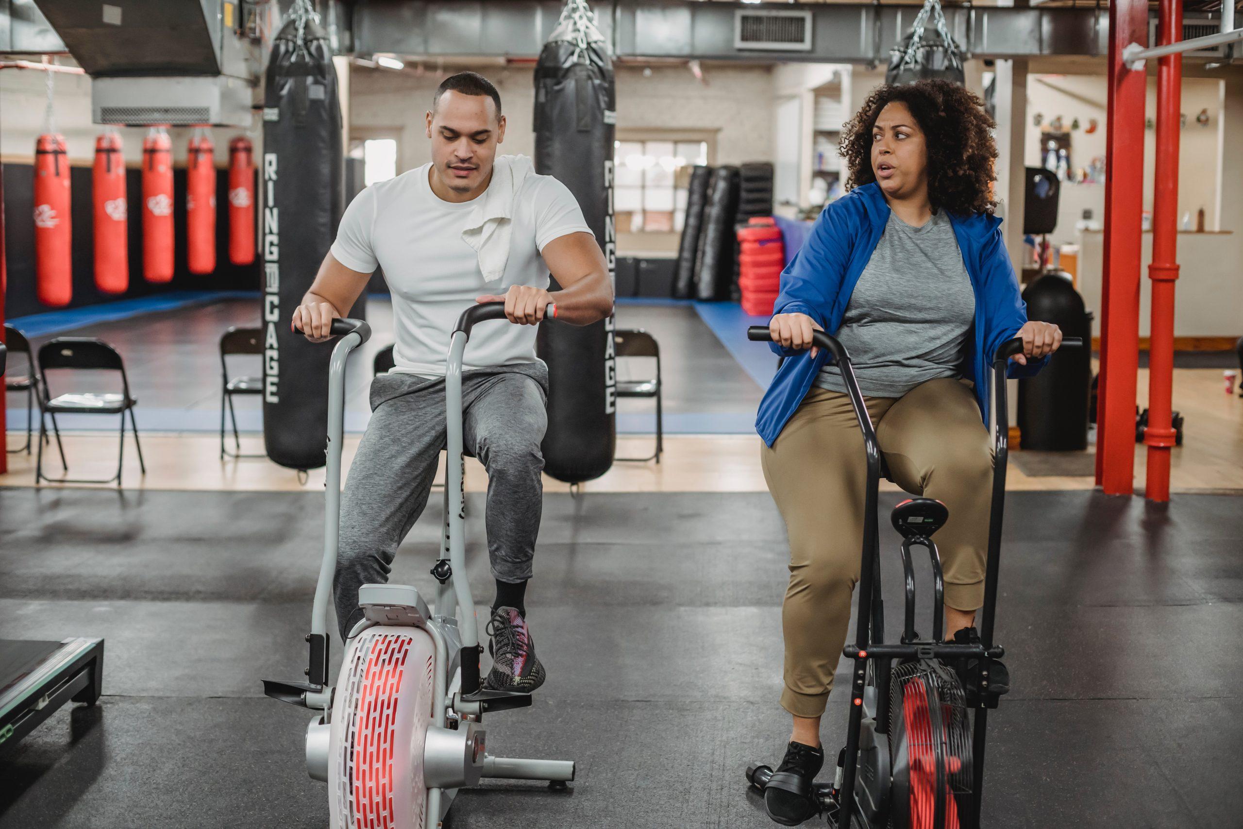 Uma mulher e um homem fazendo exercício em air bikes
