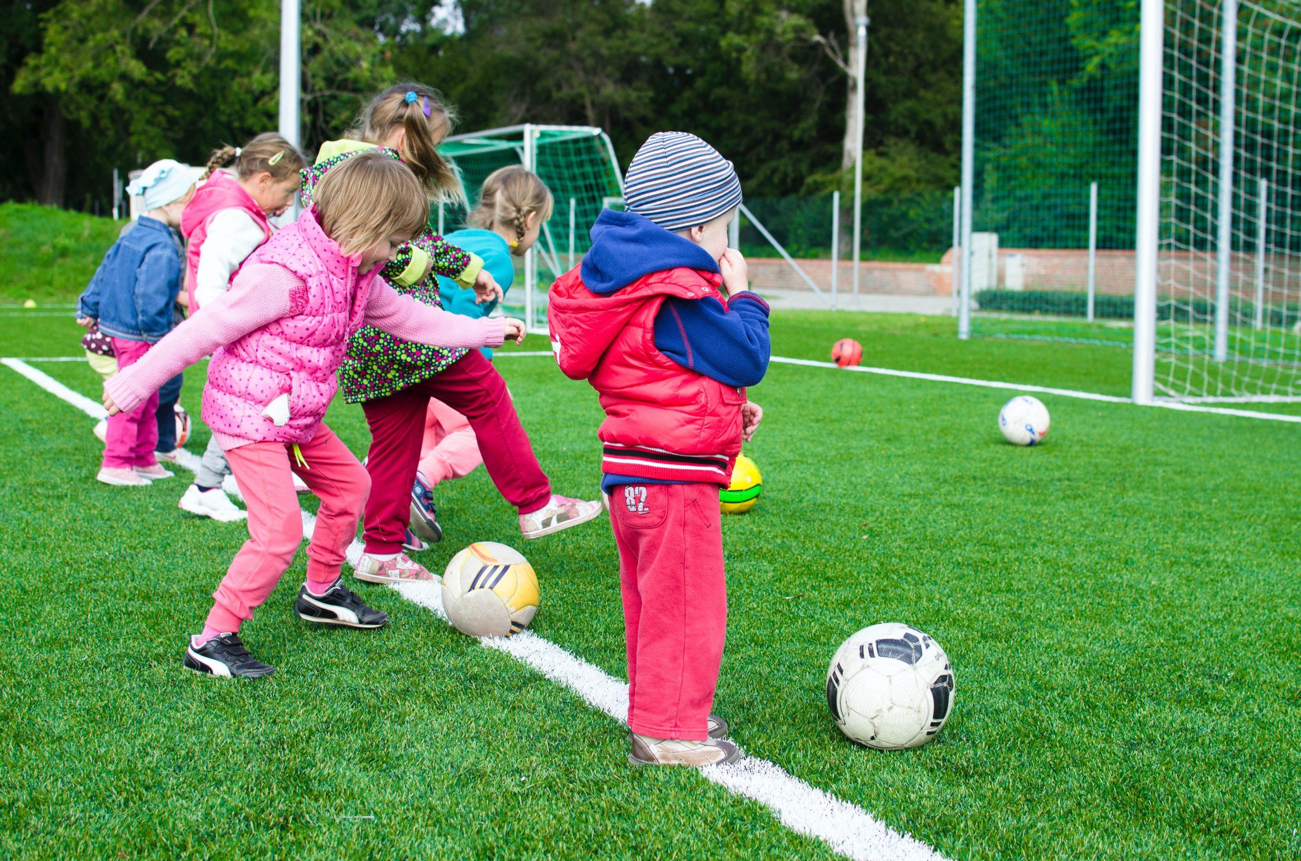 Foto com várias crianças bem pequenas chutando várias bolas ao gol