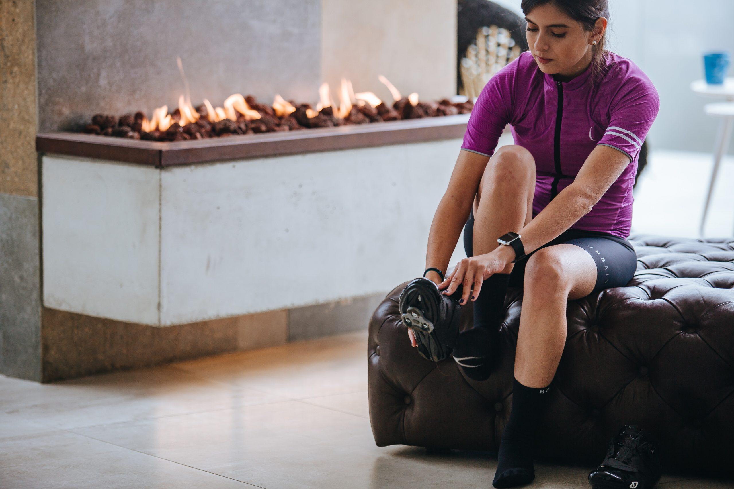 Mulher sentada no sofá com roupa de ciclismo colocando seu tênis