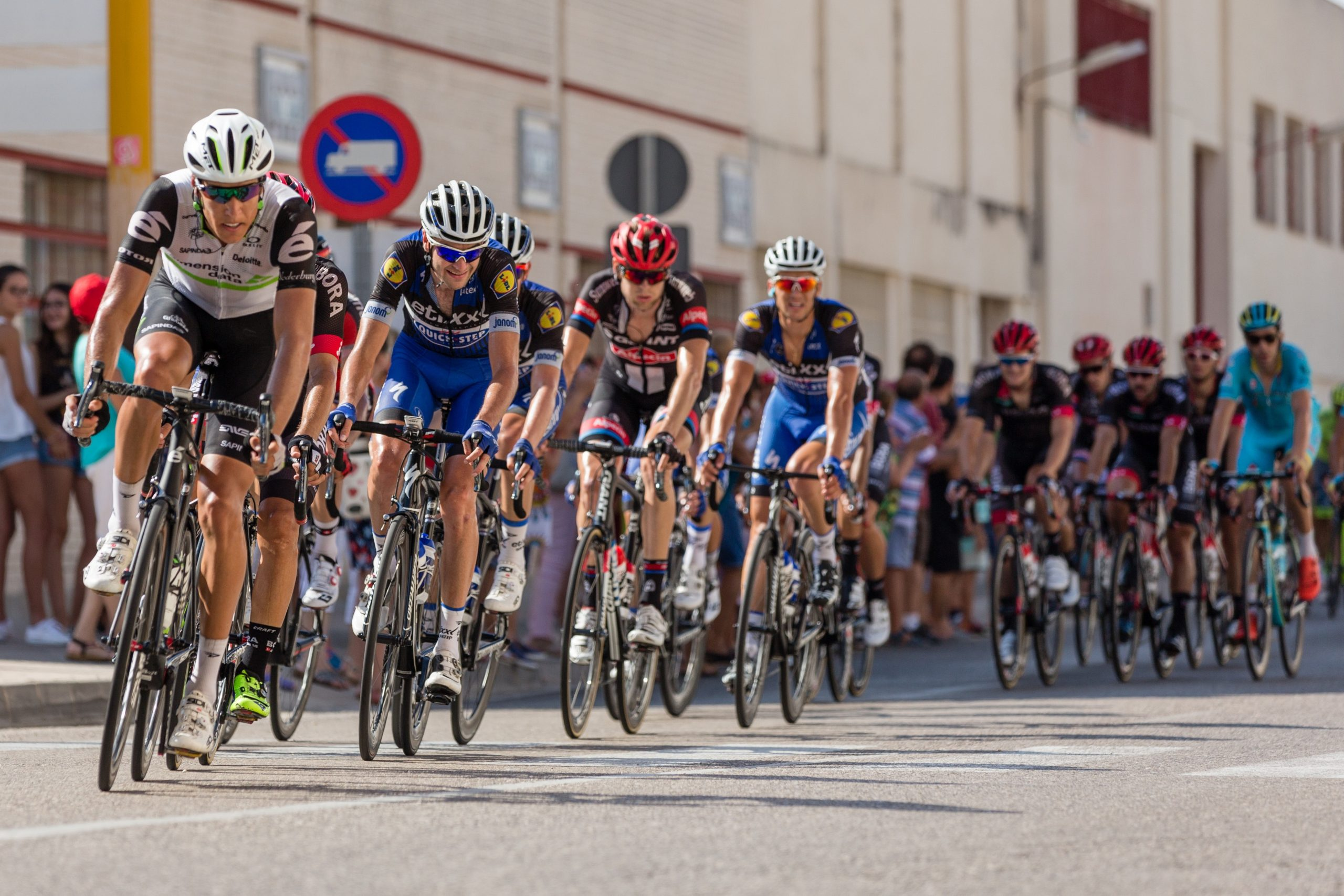 Vários ciclistas uniformizados realizando um percurso na rua