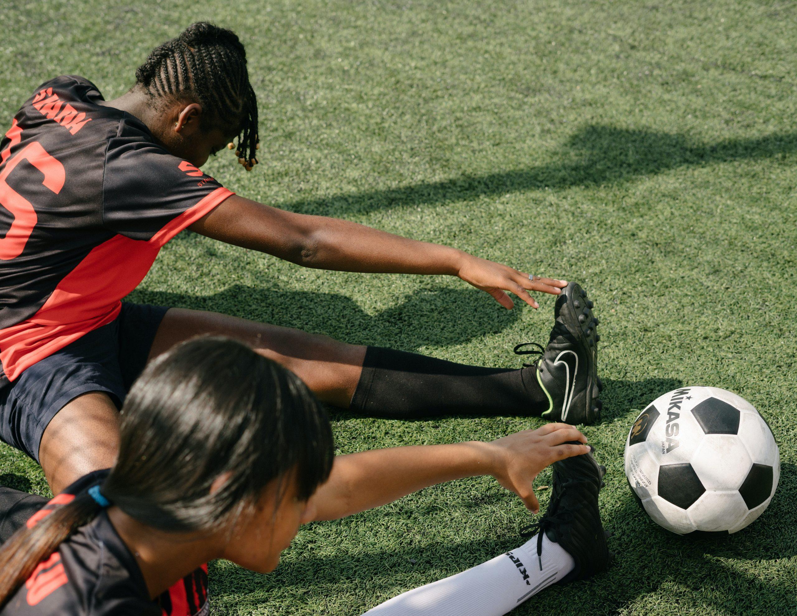Foto mostra duas meninas se alongando para uma partida de futebol