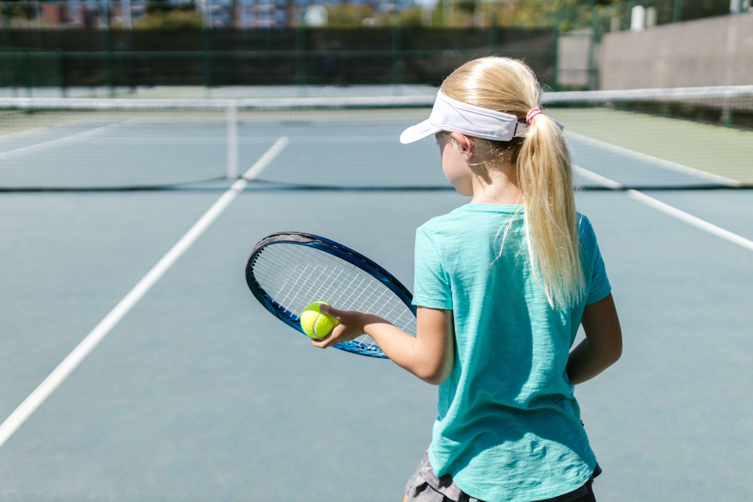 Menina de costas segurando uma bolinha e uma raquete