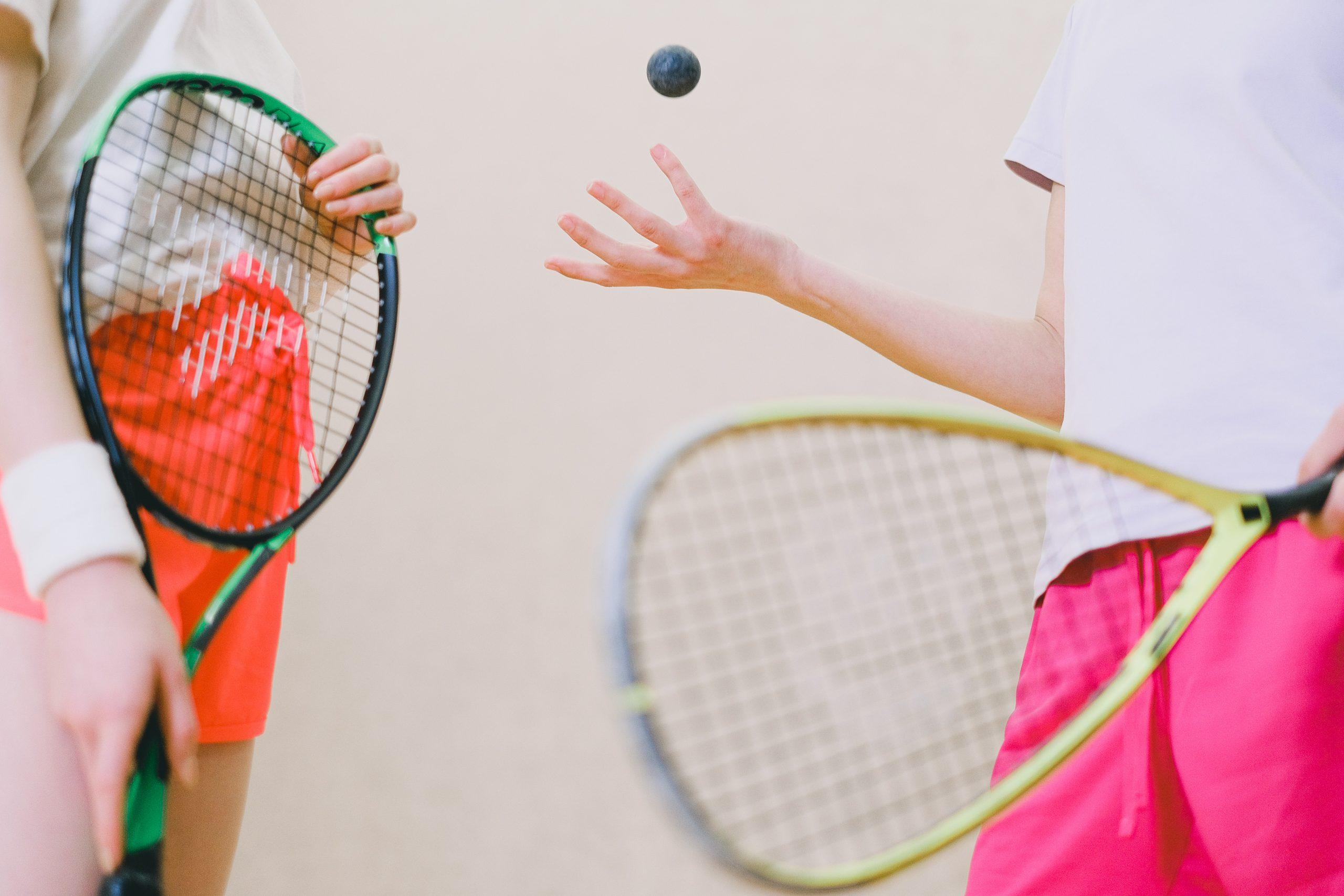 Foto de duas atletas de squash, da cabeça para baixo, segurando as raquetes. Uma delas joga a bolinha de borracha para cima.
