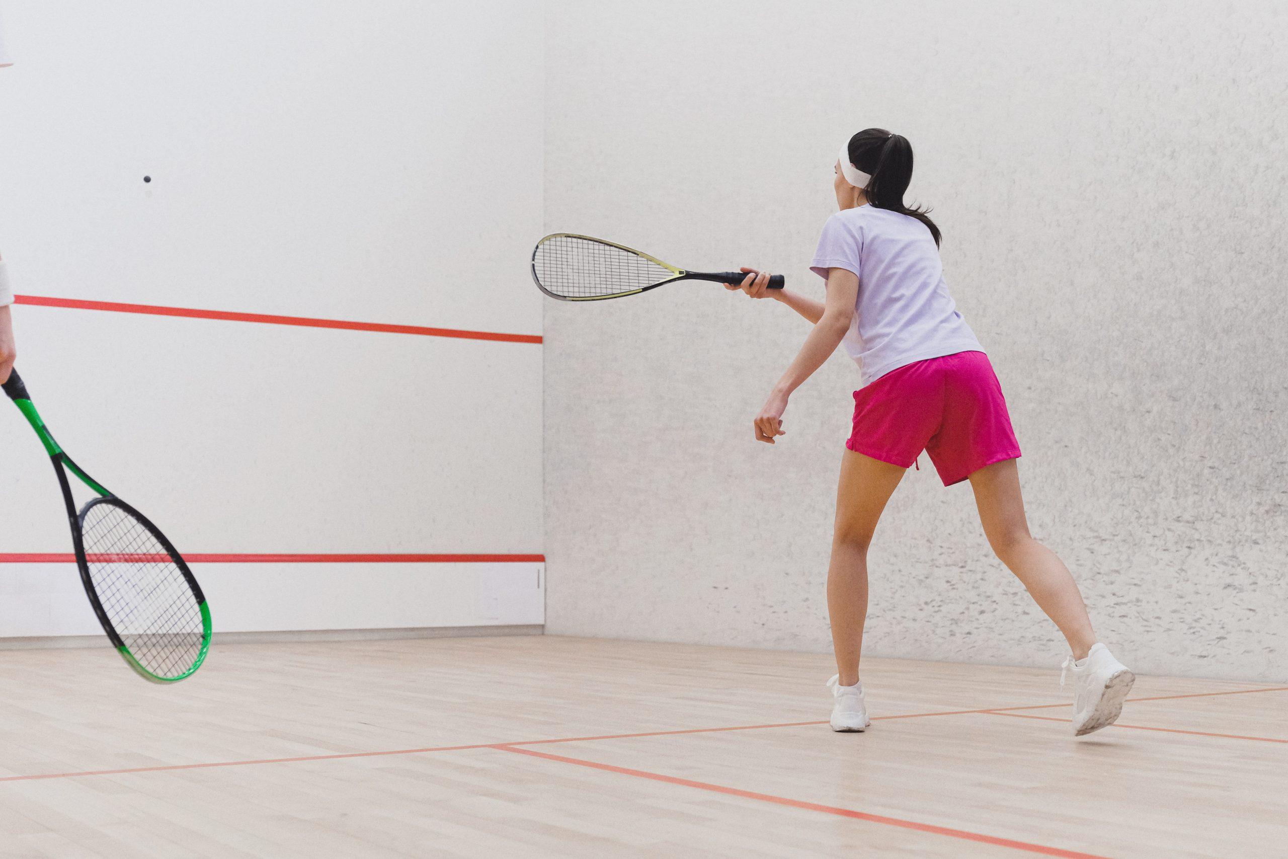 Duas pessoas jogando Squash em uma quadra com paredes de concreto