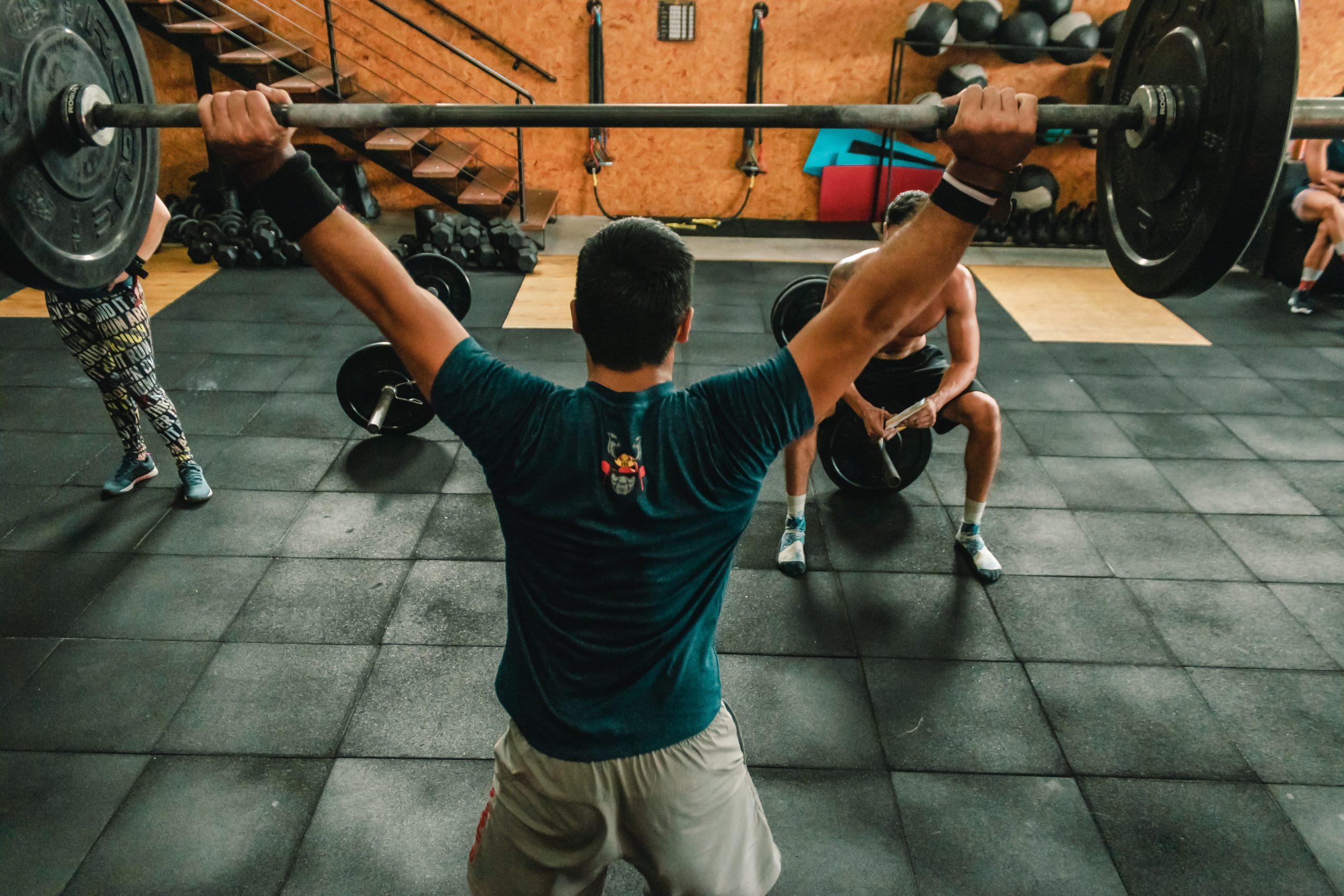 Foto de um atleta dentro de um box de Crossfit, realizando o Workout of the Day