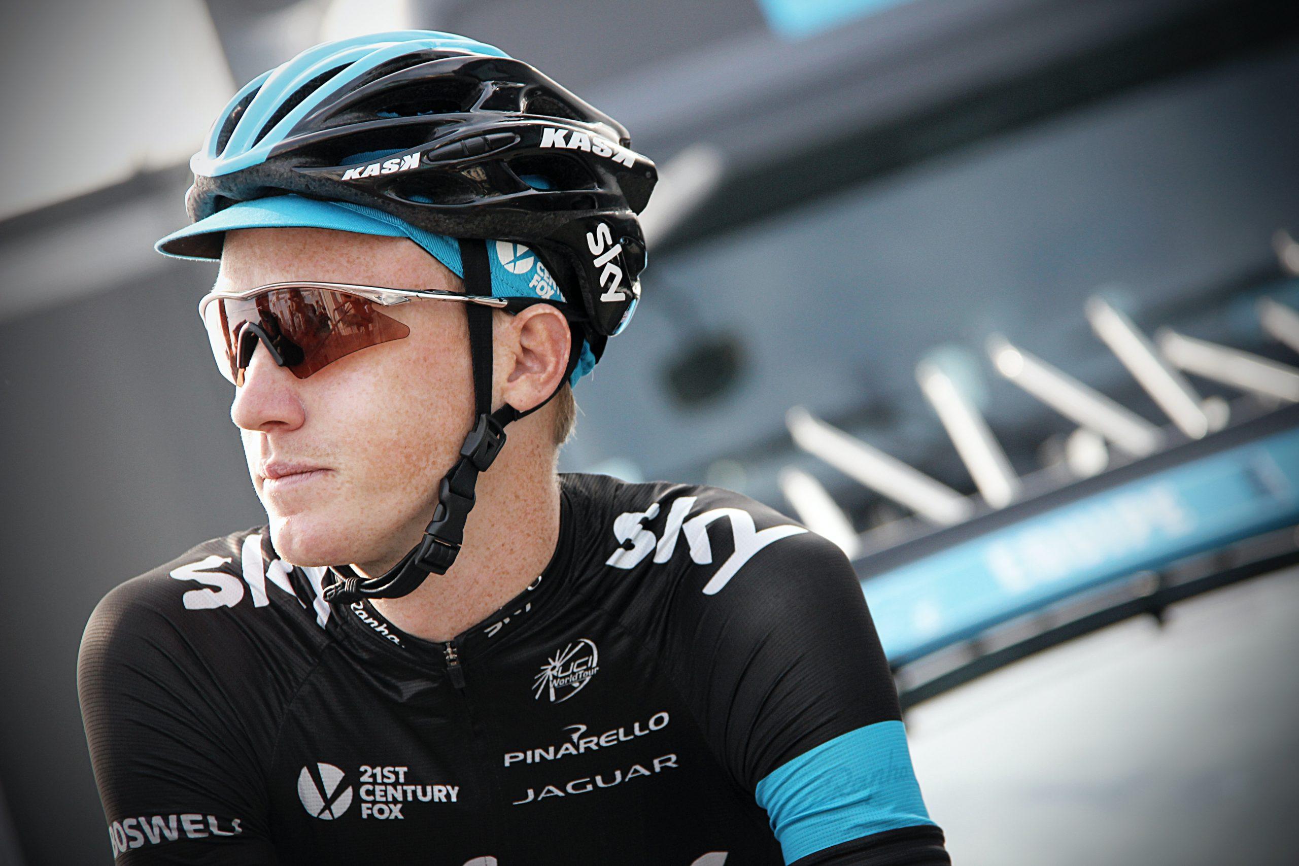 A foto mostra um ciclista olhando para o lado. Ele está com capacete e os óculos de ciclismo