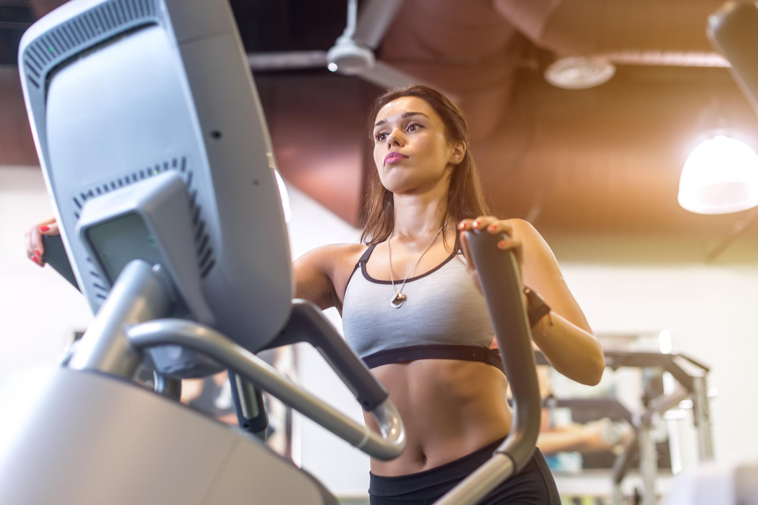 Foto de uma mulher fazendo exercícios em um simulador de caminhada