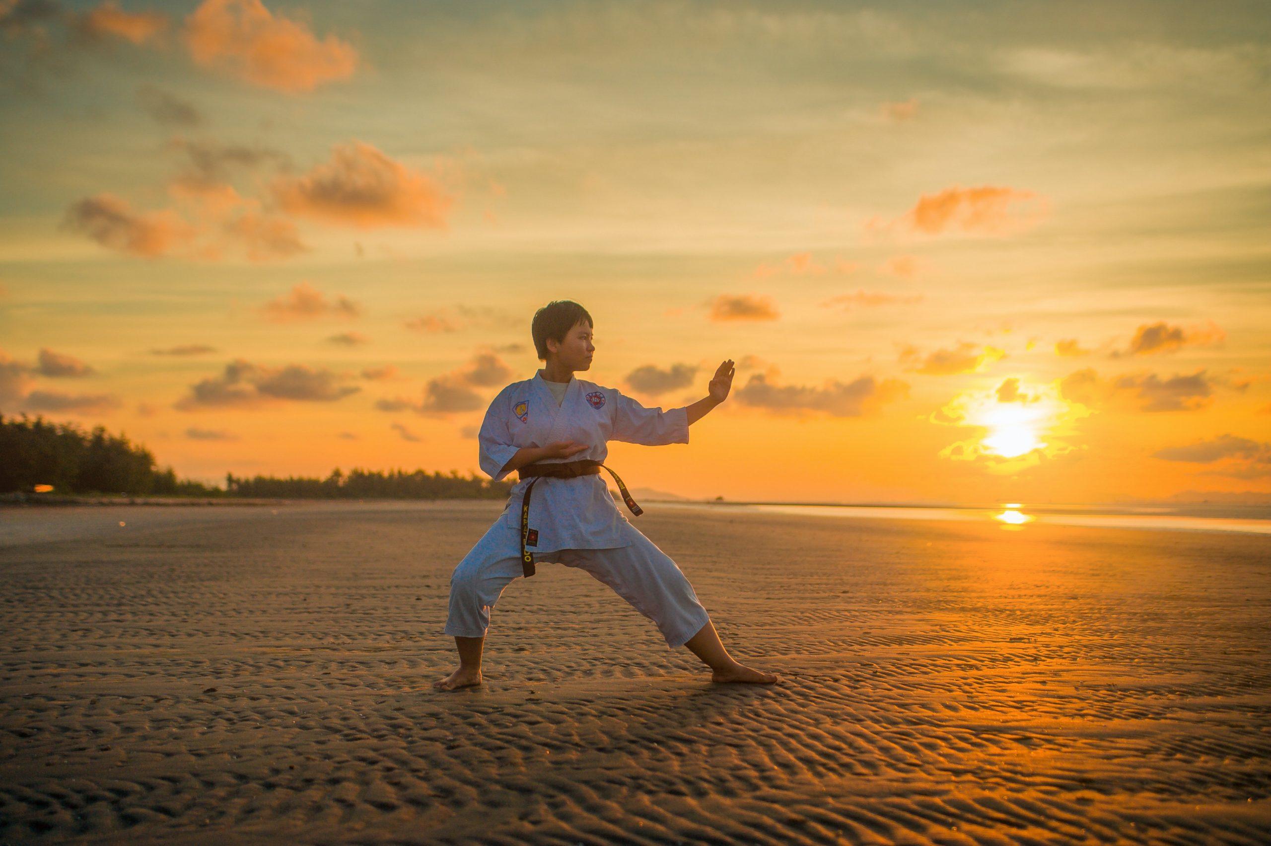A foto mostra um garoto praticando karatê ao ar livre na areia da praia