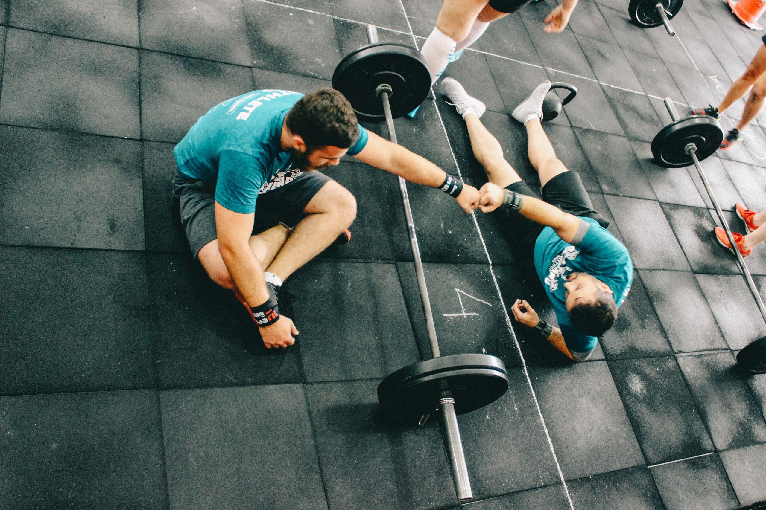 Foto de duas pessoas no chão, se cumprimentando, aparentemente após finalizar o treino de Crossfit