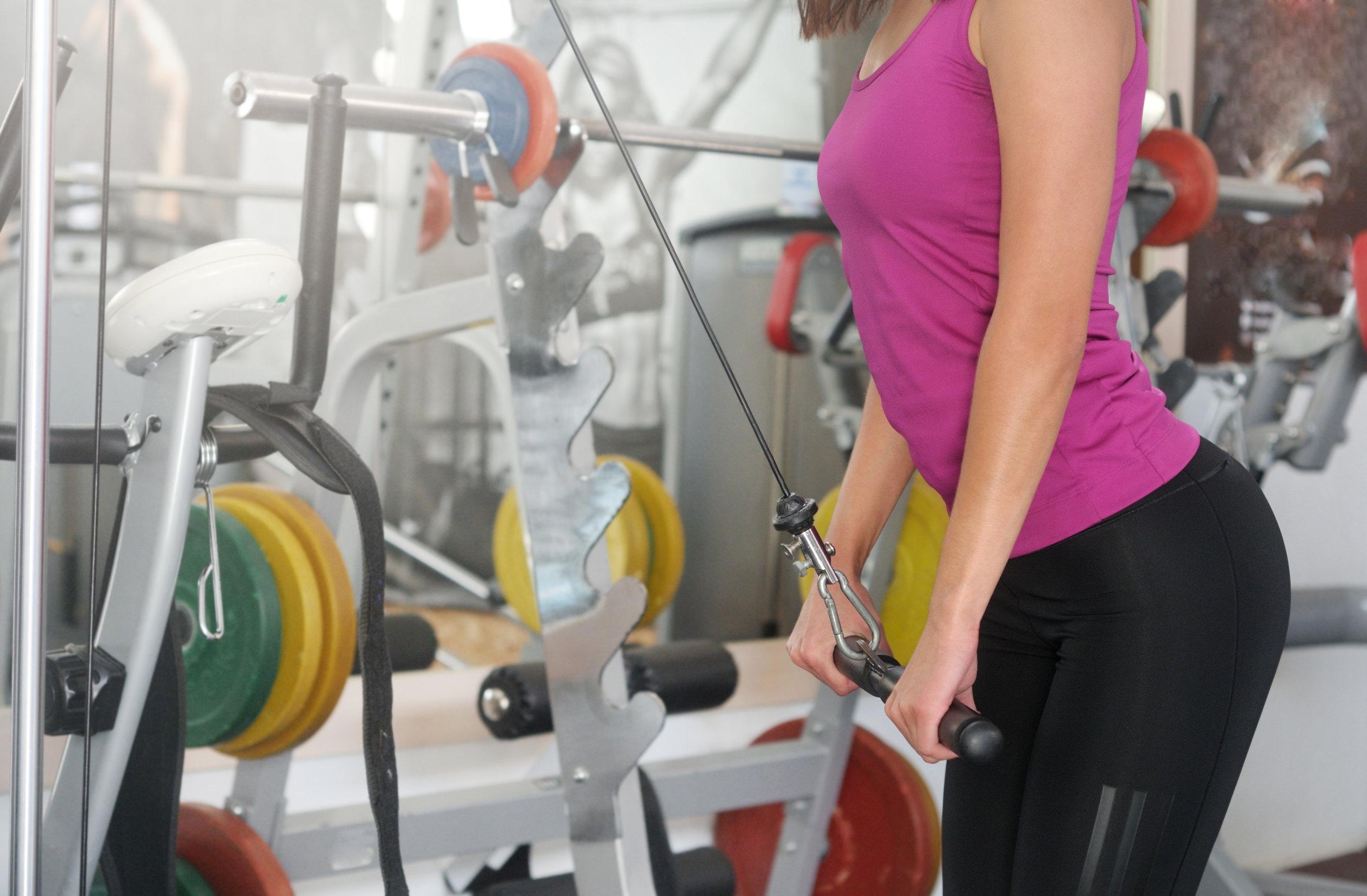 Mulher com roupa esportiva fazendo exercícios em uma estação de musculação