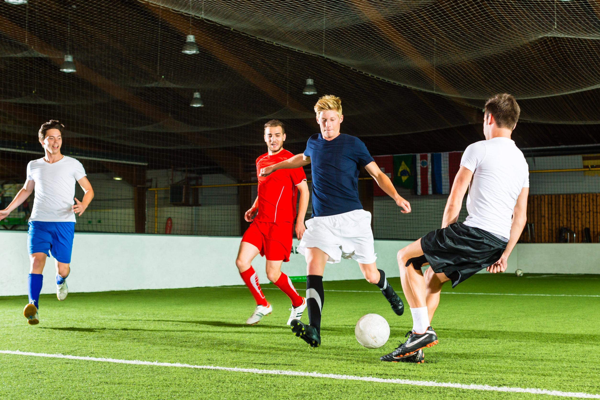 A foto mostra um jogo entre amigos de futebol society, com um garoto se preparando para o chute
