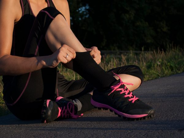 beautiful young woman pulling up socks is getting ready to run outdoors