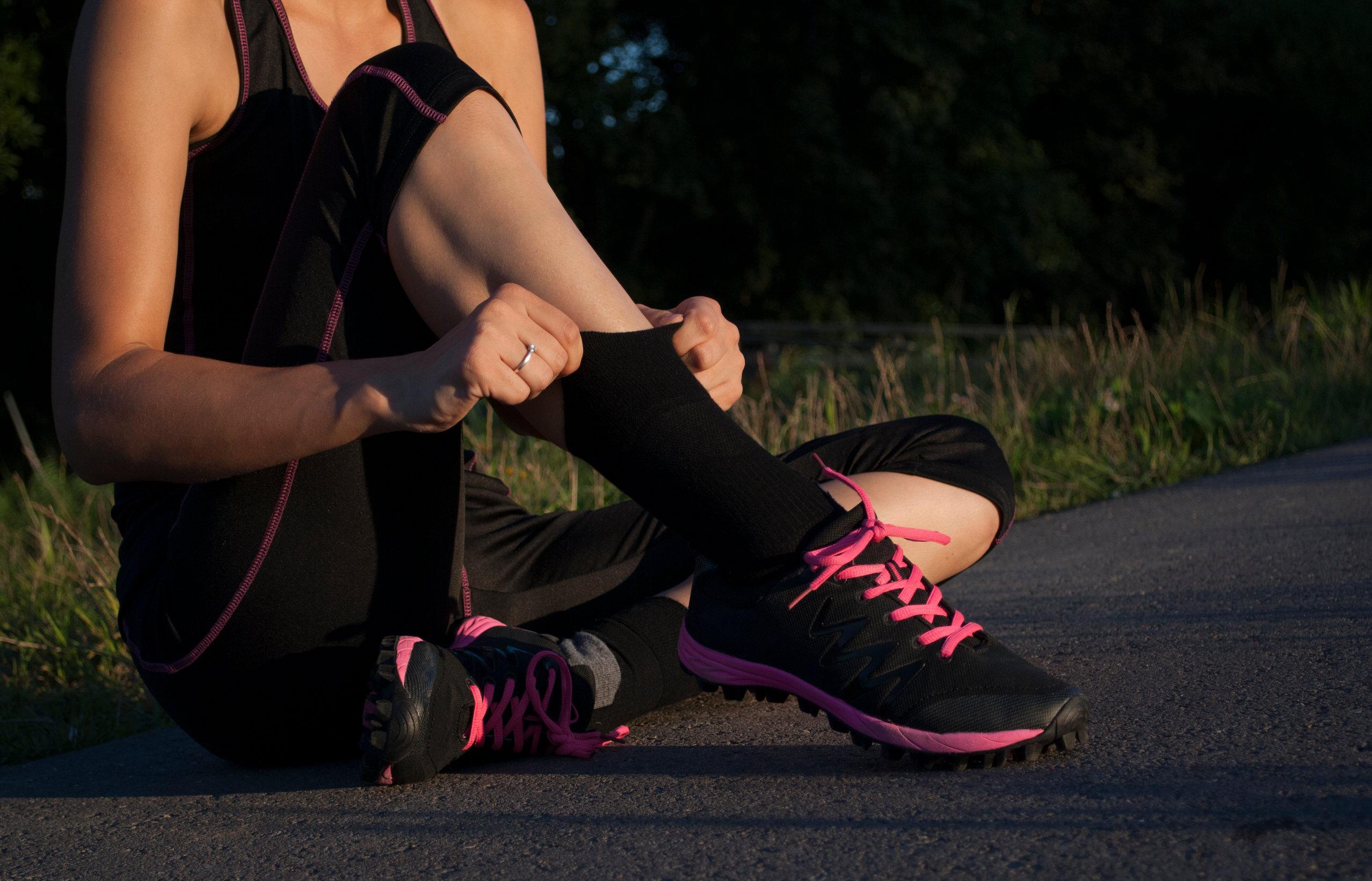 Mulher sentada no asfalto ajeitando sua meia