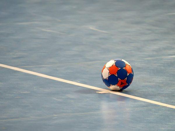 Modern colored handball ball on blue field