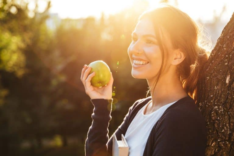 Mujer comiendo manzana verde