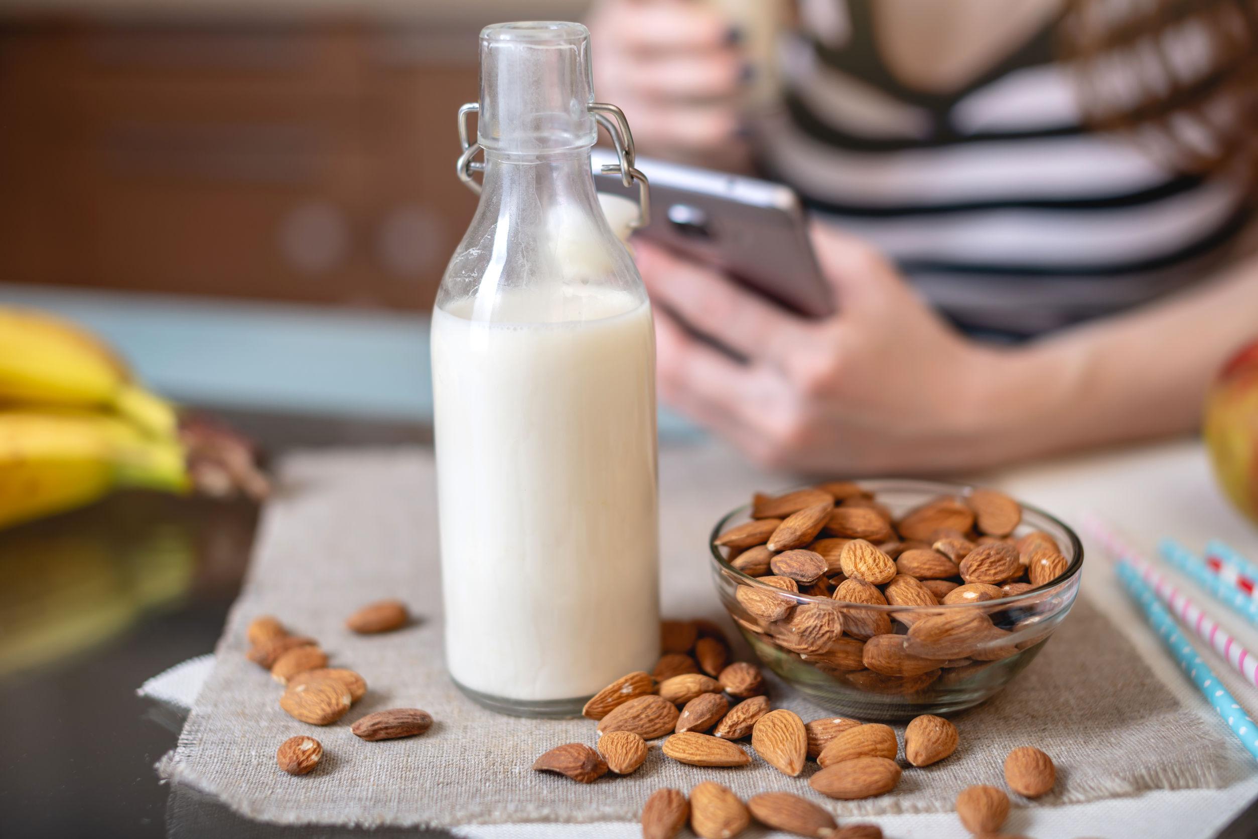 Imagen de leche de almendra en bortella y almendras junto a ella, atras una érsona sosteniendo el móvil