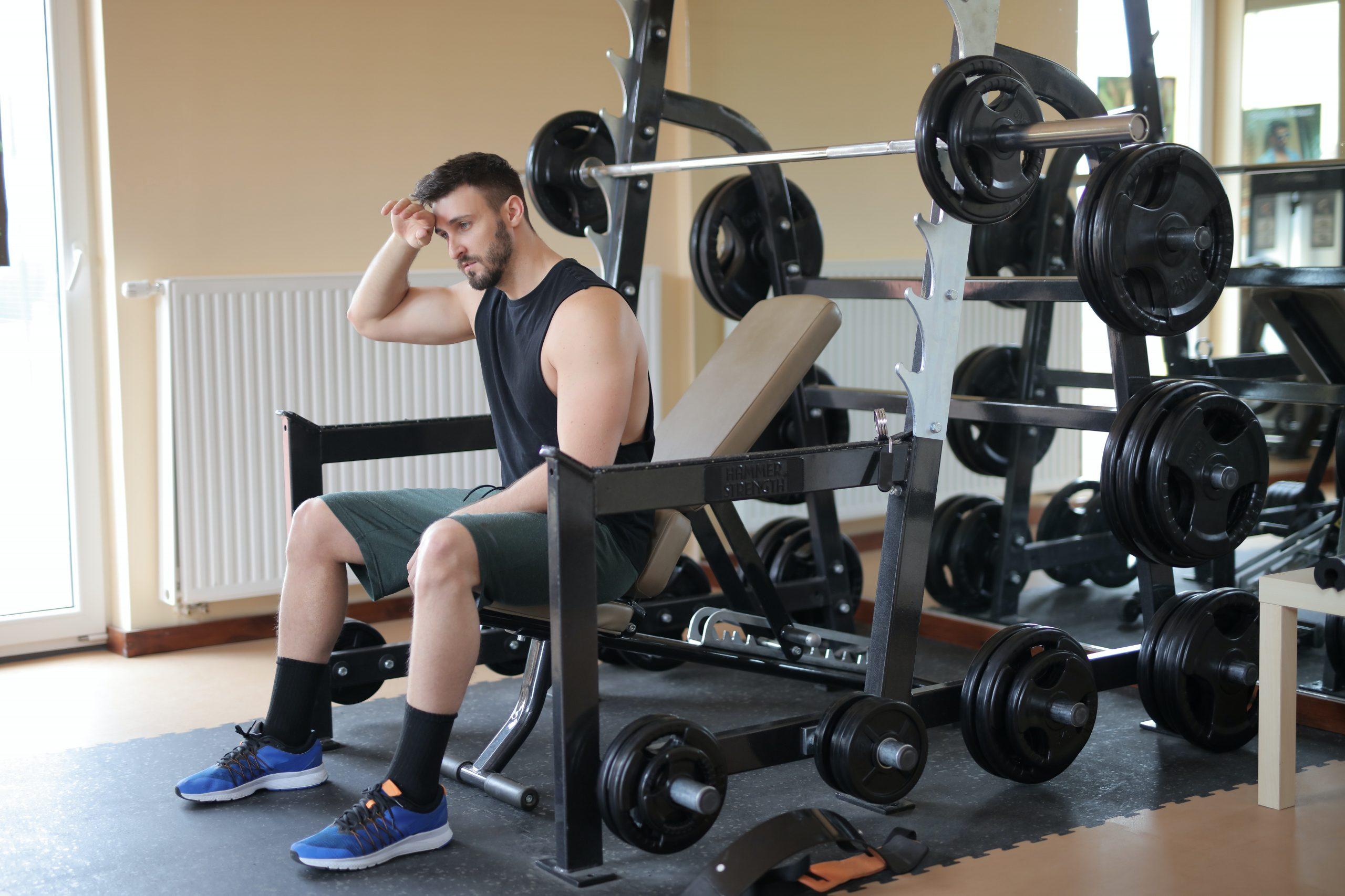 Homem com roupa esportiva sentado no banco da estação de musculação após fazer exercícios