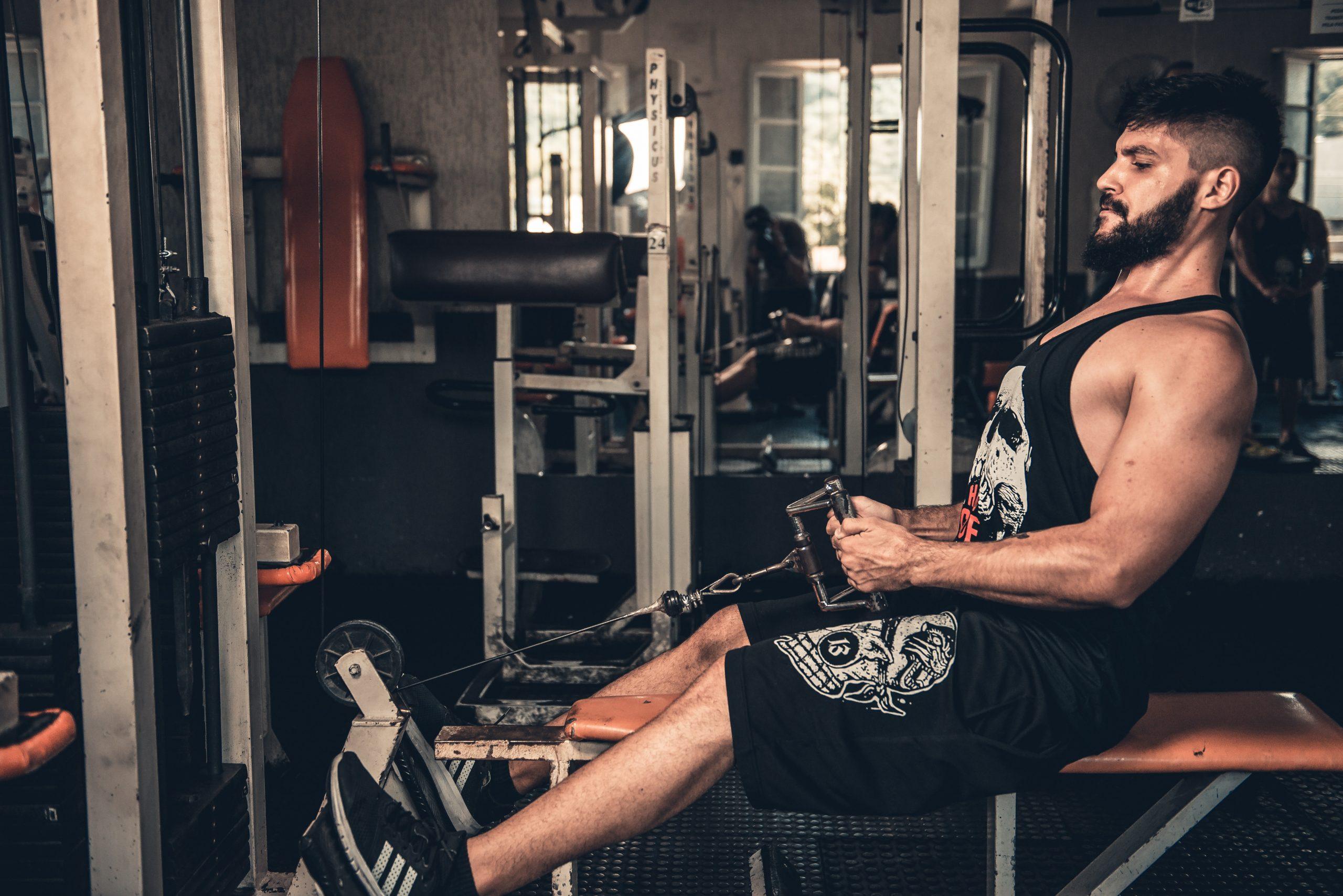 Homem com roupa esportiva fazendo movimento de remada na estação de musculação