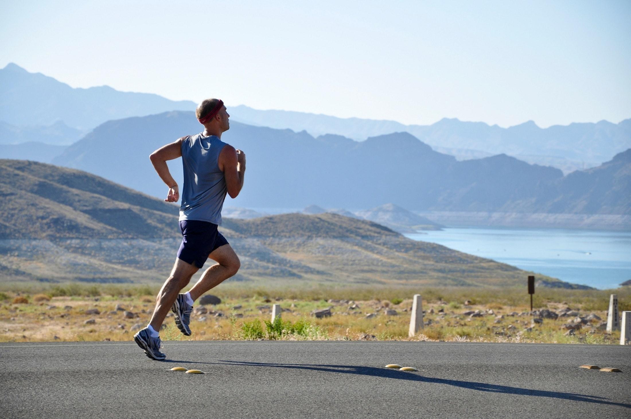 Homem com roupa esportiva correndo na rua