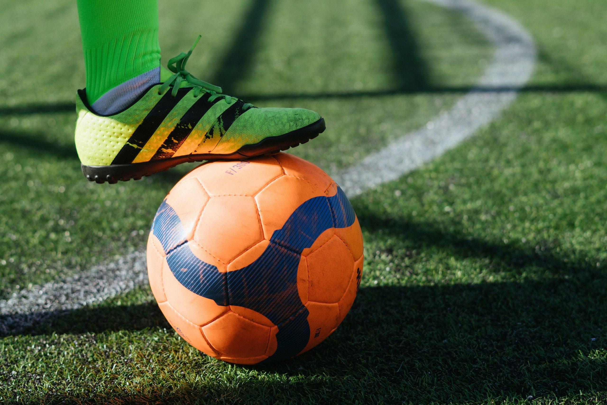 Foto mostra uma bola de futebol society laranja no gramado. Um jogador está com a perna em cima dela.