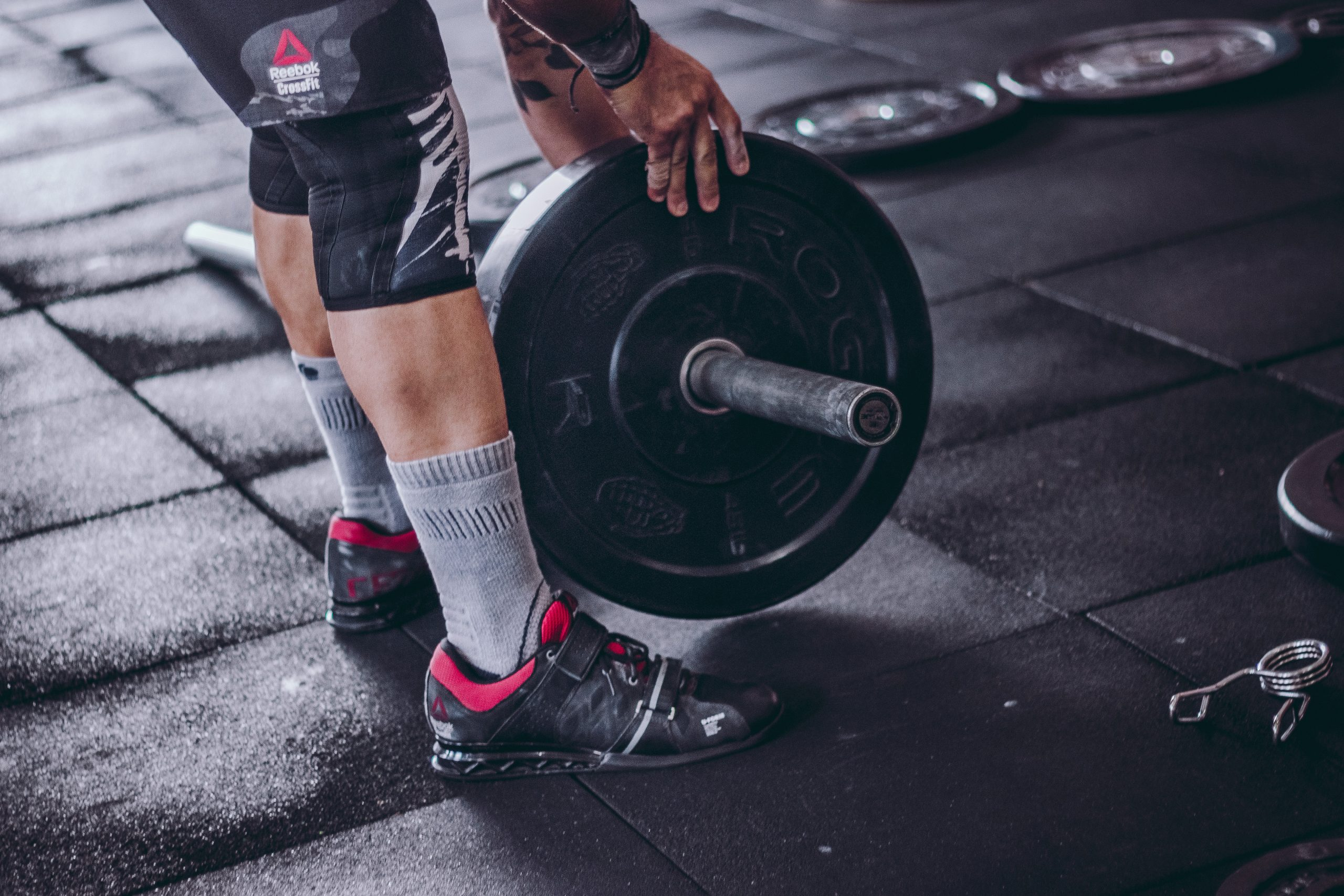 Homem pegando barra de peso no chão da academia