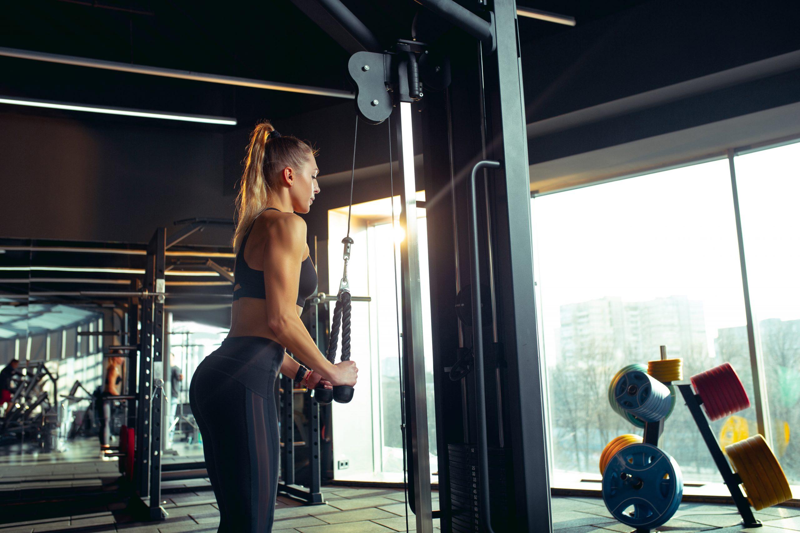 Mulher com roupa esportiva de pé na academia fazendo exercício com as cordas da estação de musculação