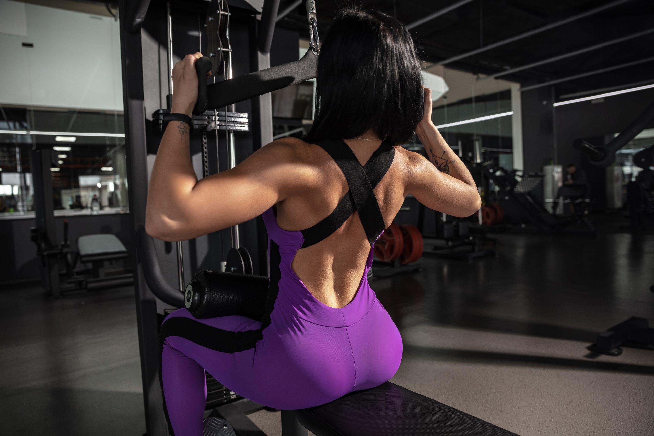 Mulher de costas com roupa esportiva sentada na estação de musculação puxando pesos